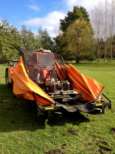 Tree shaking machine in a grassy paddock.