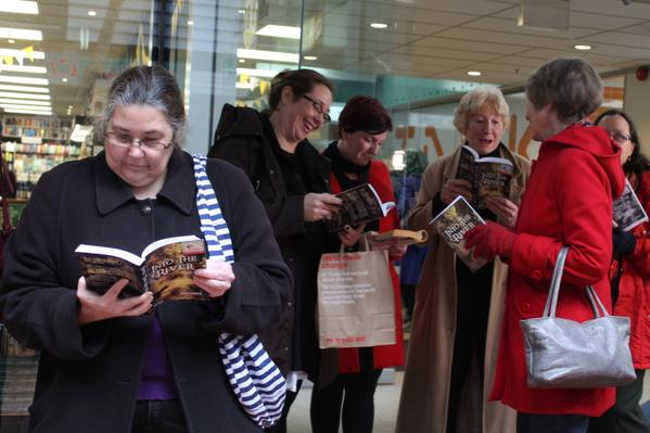 People reading 'Into the River' in a protest against book banning